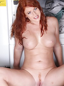 Wavy-haired redhead with blue eyes masturbating next to a washer